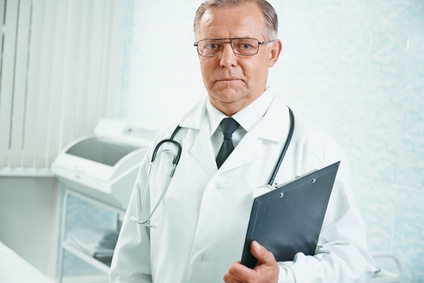 Portrait of senior male doctor with documents in hospital